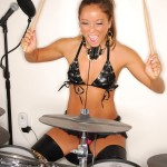 midori west in a black bikini playing drums